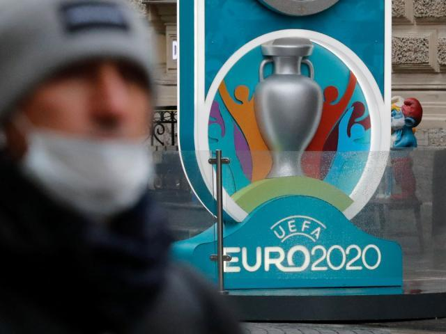 0_A-person-wearing-a-protective-face-mask-walks-past-the-Euro-2020-countdown-clock-in-Saint-Petersburg.jpg